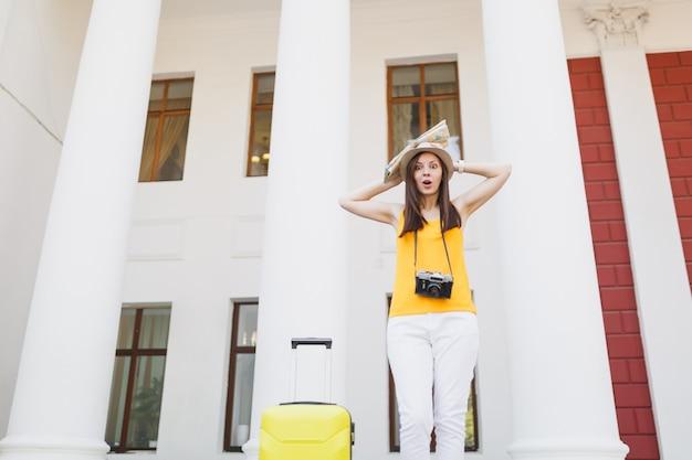 スーツケースのレトロなビンテージ写真カメラが頭にしがみついているカジュアルな服を着た若い驚いた旅行者の観光客の女性は、屋外の都市地図を保持します。週末の休暇で海外旅行する女の子。観光の旅のライフスタイル。