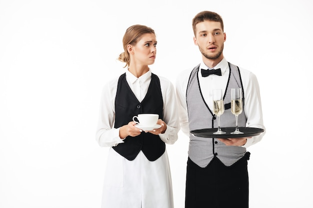 Young amazed waiter holding tray with glasses of champagne