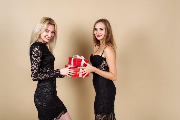 베이지 색 배경 위에 고립 된 그녀의 여자 친구와 함께 크리스마스를 축 하하는 동안 현재 들고 젊은 놀된 여자.