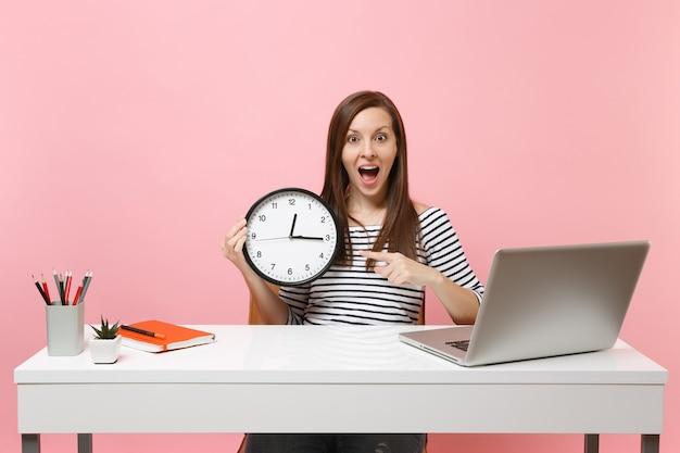Молодая удивленная женщина, указывая указательным пальцем на круглые часы-будильник, сидит за белым столом с современным ноутбуком, изолированным на пастельно-розовом фоне. достижение бизнес-концепции карьеры. скопируйте пространство.