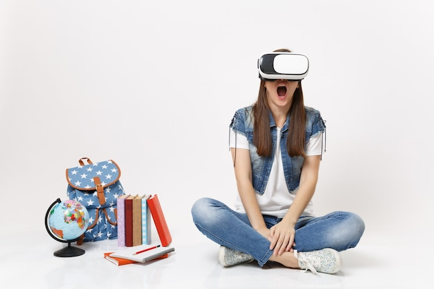 Giovane studentessa stupita che indossa occhiali per realtà virtuale che urla godendosi seduta vicino al globo, zaino, libri scolastici isolati