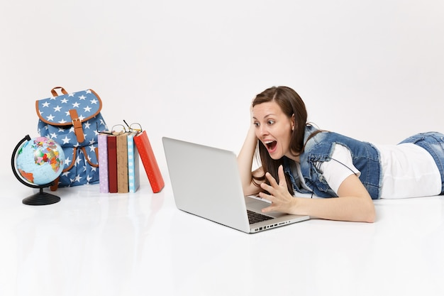 Young amazed woman student working on laptop pc computer spreading hand and lying near globe, backpack, school books isolated