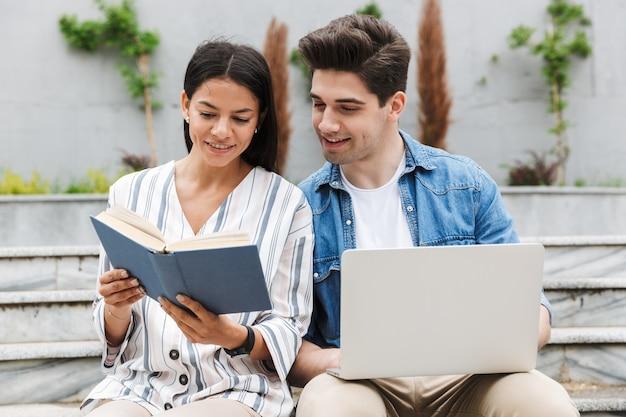 Молодые удивительные любящие пары деловых людей коллеги на открытом воздухе снаружи на шагах, используя портативный компьютер, читая книгу.