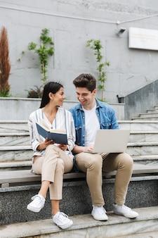 若い驚くべき愛情のあるカップルのビジネスマンの同僚は、ラップトップコンピューターの読書本を使用してステップで屋外の外で。