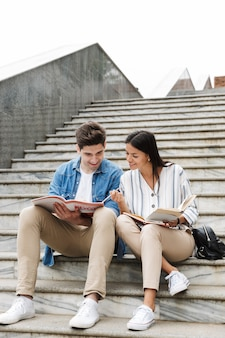 Young amazing loving couple students colleagues outdoors outside on steps reading book writing notes studying.