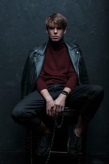 金属の銀の鎖が付いているスニーカーのスタイリッシュなジーンズの赤いゴルフのレトロなスタイルのジャケットの髪型の若い驚くべき男が座って、暗いスタジオの木製の椅子のカメラをのぞき込む。