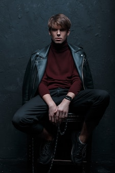Young amazing man with a hairstyle in a retro-style jacket in red golf in stylish jeans in sneakers with a metal silver chain sits and looks into the camera on a wooden chair in a dark studio.guy