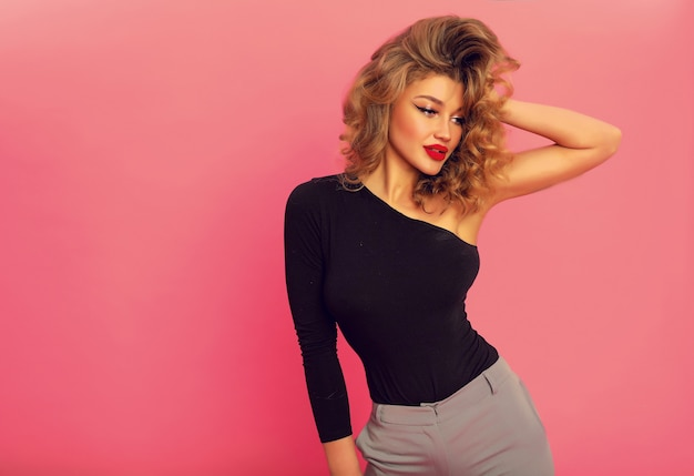 Young amazing model in black top with one sleeve and grey pants. touching her volume curly hair, stylish makeup with red lips. shapely sexy body.