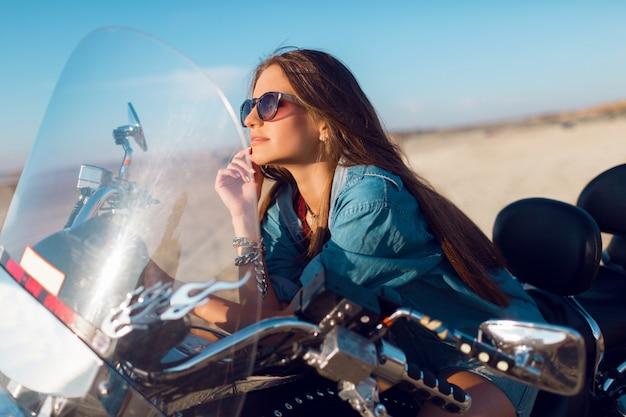 スタイリッシュなクロップトップ、シャツを着て、ビーチでバイクに座っている若い驚くべきセクシーな女性は、スリムな飼いならされた体と長い髪にぴったりです。アウトドアライフスタイルの肖像画。
