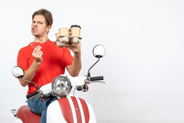 Giovane uomo ambizioso del corriere in uniforme rossa che tiene ordine e carta di credito sulla parete gialla