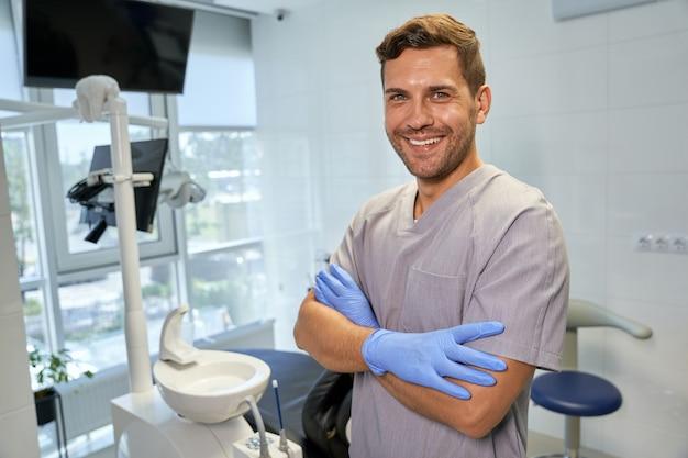 Молодой амбициозный дантист выглядит счастливым на своем рабочем месте