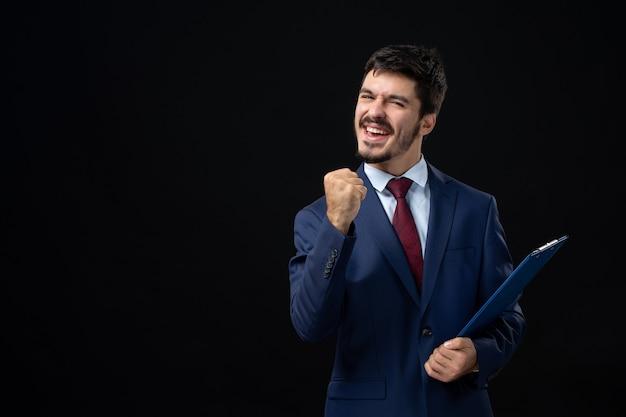 Молодой амбициозный офисный работник мужского пола в костюме держит документы и наслаждается своим успехом на изолированной темной стене