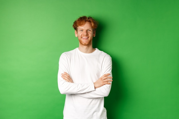 Young ambitious man with red hair standing over green background, holding hands crossed on chest and smiling.