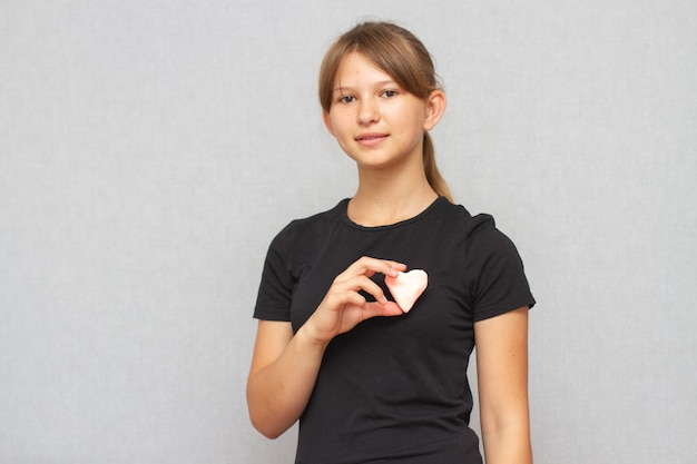 Young american girl child holding plasticine heart in her hands.