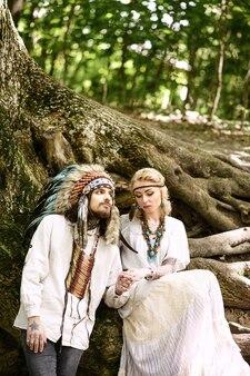 큰 나무 근처 숲에서 손을 잡고 젊은 아메리칸 인디언 커플.