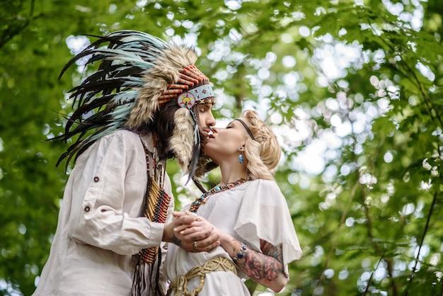 숲에서 키스하는 젊은 아메리칸 인디언 부부