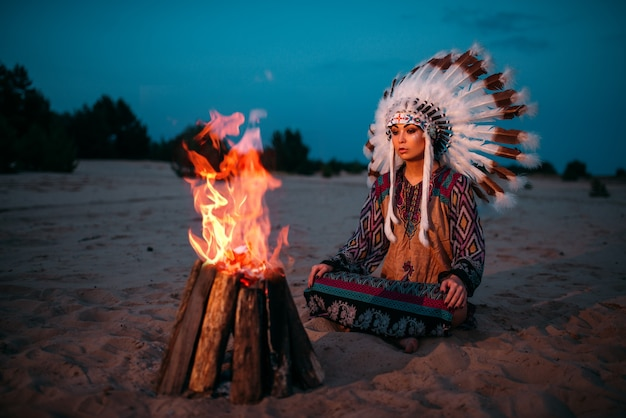 Young american indian woman against fire, cherokee, navajo. headdress made of feathers of wild birds. night ritual