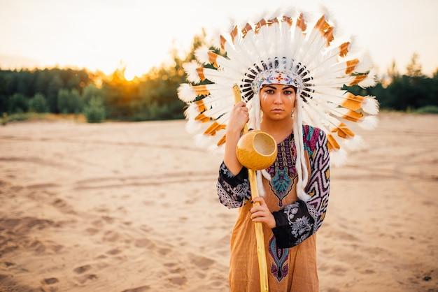 野鳥の羽で作られた伝統的な衣装と頭飾りの若いアメリカインディアンの女性