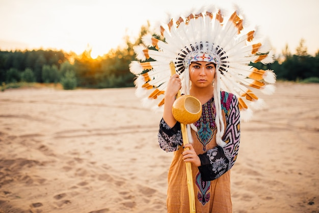 Young american indian woman in traditional costume and headdress made of feathers of wild birds