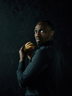 Young american man eating hamburger and looking away on black studio background