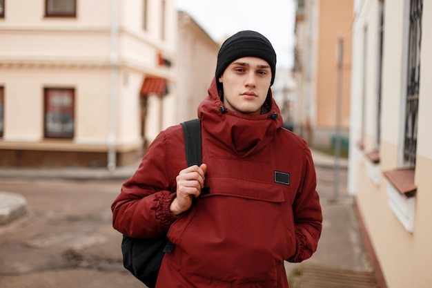 Young american man in a stylish knitted hat in a fashionable red long jacket with a black backpack is standing on the street near vintage buildings