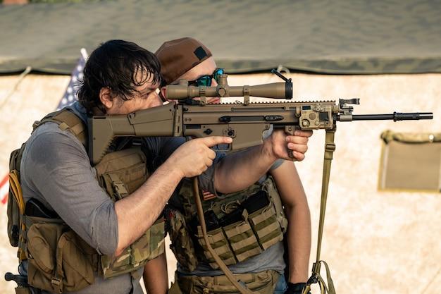 군 기지에서 총격을 가하기 전에 조끼와 모자를 쓰고 소총을 확인하는 젊은 미국 남성