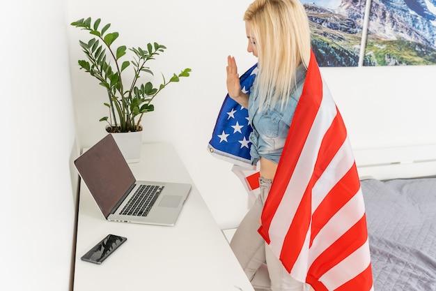 그녀의 노트북을 사용하여 그녀의 어깨 너머로 미국 국기를 가진 젊은 미국 여자