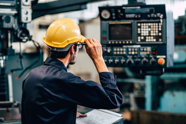 Young american worker intend to work in a heavy industrial factory looking and control machine in production line.