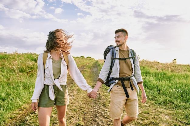 Молодая влюбленная пара в повседневной одежде разговаривает, двигаясь по проселочной дороге против облачного неба в летний день и глядя друг на друга