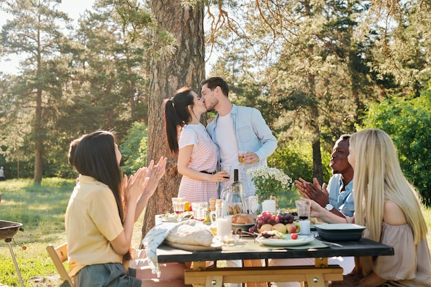 Young amorous couple kissing under pine tree by served table while their friends congratulating them with engagement by clapping hands