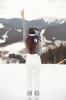 젊고 활동적인 갈색 머리 스키. 눈 덮인 산에있는 여자.