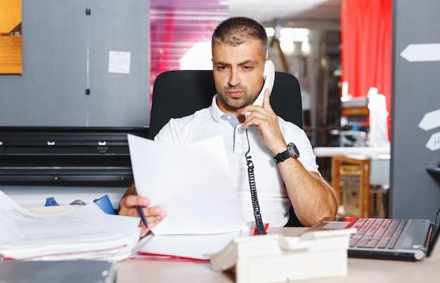 Молодой и амбициозный биржевой трейдер заключает сделку по телефону в загруженном офисе, заполненном компьютерами.
