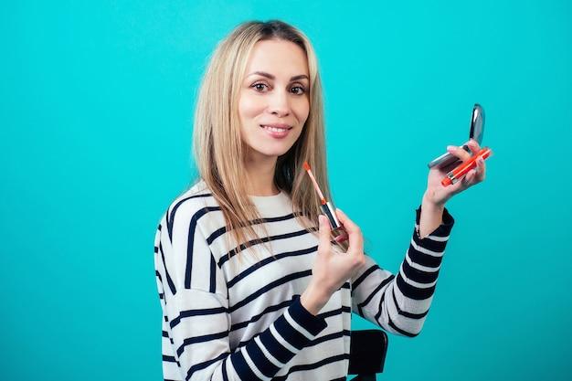 若くて魅力的なブロンドの女性visagiste(メイクアップアーティスト)の美容ブロガーは、スタジオの青い背景の唇にメイクアップリップスティックを適用しています。スキンケアと顔の美容化粧品の概念