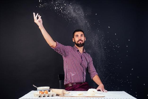 Молодой и привлекательный пекарь кавказского человека с бородой делает тесто, посыпанное мукой на черном фоне в студии. кондитер испекает торт