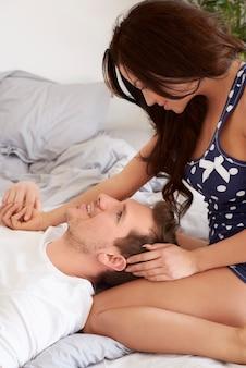 젊고 매력적인 부부는 침대에서 함께 시간을 보내고