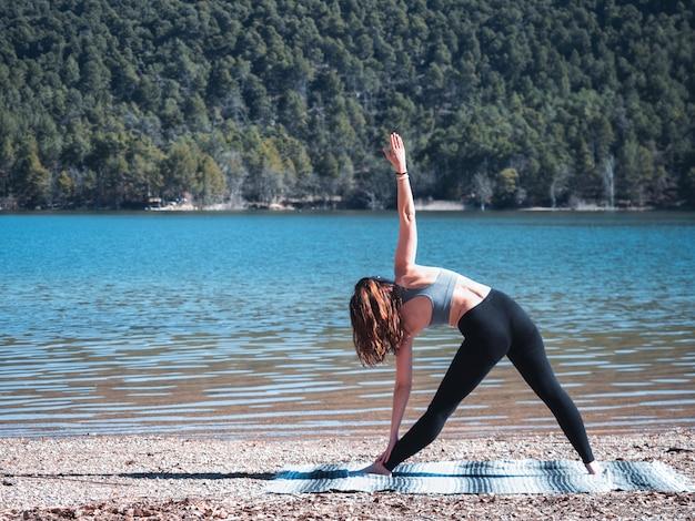 자연에 둘러싸인 호수 옆에 야외에서 요가 하 고 젊고 매력적인 여자. 건강한 생활의 개념입니다.
