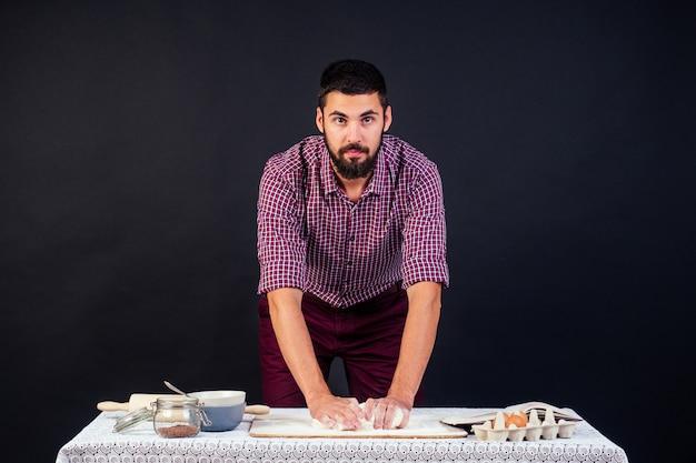 Молодой и привлекательный итальянский пекарь с бородой делает тесто, посыпанное мукой итальянской пиццы на черном фоне в студии. кондитер испекает торт