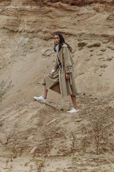 曇りの日に砂場でフルハイトポーズをとるベージュの秋の服装の若くて魅力的な混血の女性。