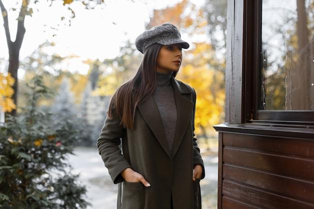 灰色のエレガントなコートと灰色のヴィンテージキャップの若くて魅力的なスタイリッシュな女の子は、公園で屋外でリラックスします。ファッショナブルな女性。