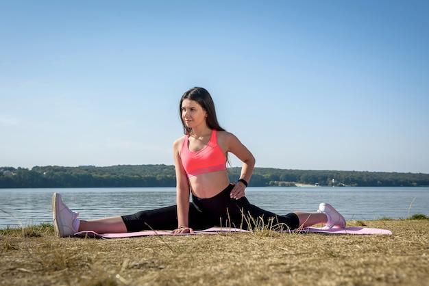 昼間に湖の近くの草の上にウォームアップのより糸を伸ばすスポーツウェアの若くて魅力的な女性。健康的な生活様式