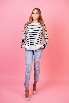 ピンクの背景にスタジオでジーンズ、かかとの高い靴、セーターでポーズをとる若くて魅力的な女性のスタイリッシュなモデル