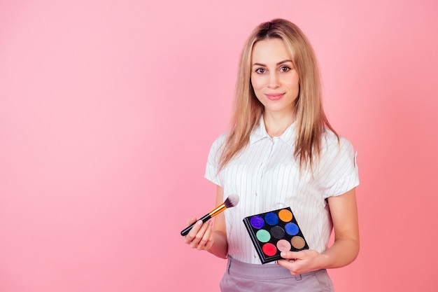 若くて魅力的な女性visagiste(メイクアップアーティスト)の美容ブロガーがスタジオでピンクの背景の顔にメイクをしています。スキンケアと顔の美容装飾化粧品の概念