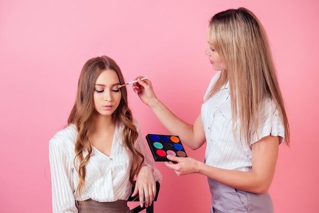 젊고 매력적인 여성 visagiste(메이크업 아티스트)는 스튜디오에서 분홍색 배경의 모델 뷰티 블로거를 위해 메이크업을 적용하고 있습니다. 얼굴 피부 관리 및 미용 장식 화장품의 개념