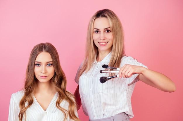 젊고 매력적인 여성 비자지스트(메이크업 아티스트)가 스튜디오에서 분홍색 배경의 모델을 위해 메이크업을 하고 있습니다. 피부 관리와 아름다움의 개념