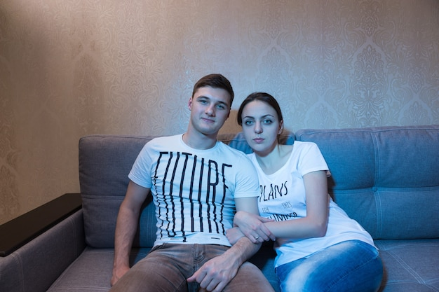 젊고 매력적인 부부는 편안한 분위기에서 Tv 앞에 함께 소파에 앉아 Tv를 봅니다. 프리미엄 사진