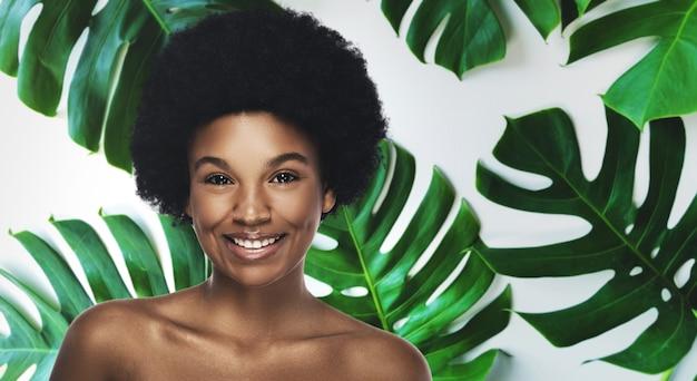 熱帯の葉に完璧な滑らかな肌を持つ若くて美しいアフリカの女性。自然派化粧品とスキンケアのコンセプト。