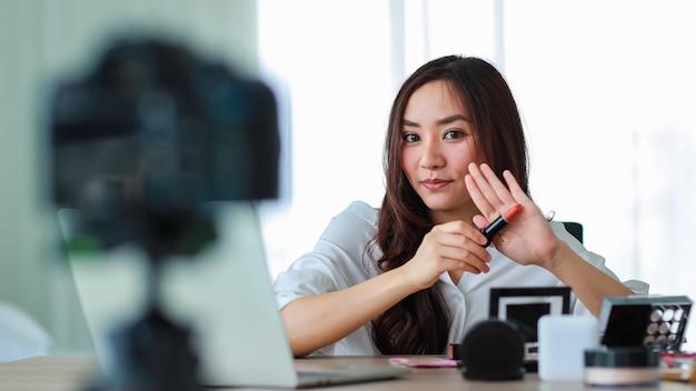 Молодая и красивая азиатская девушка показывает помаду на камеру и сравнивает с цветом кожи во время трансляции или записи видео об обзоре косметики и бьюти-блогере. интернет-продажи и концепция маркетинга.
