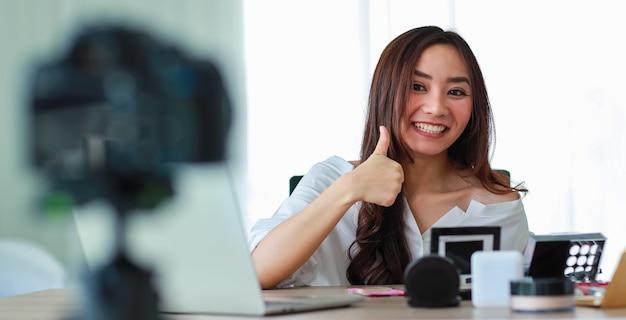 Молодая и красивая азиатская девушка разговаривает и машет рукой на камеру с улыбающимся лицом и счастлива во время трансляции видеозаписи о косметическом содержании и обзоре. интернет-продажи и концепция маркетинга.