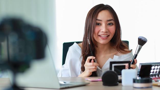 Молодая и красивая азиатская девушка разговаривает с камерой с улыбающимся лицом и счастлива во время трансляции видеозаписи о косметическом содержании и обзоре. интернет-продажи и концепция маркетинга.