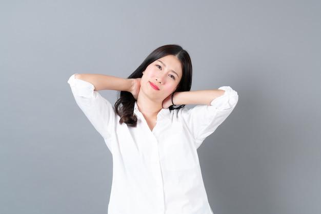 Молодая и красивая азиатская женщина болит от офисного синдрома в белой рубашке на сером